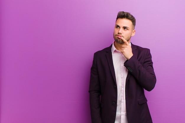 Junger hispanischer mann mit dem überraschten, nervösen, besorgten oder erschrockenen blick, schauend zur seite in richtung zum kopienraum