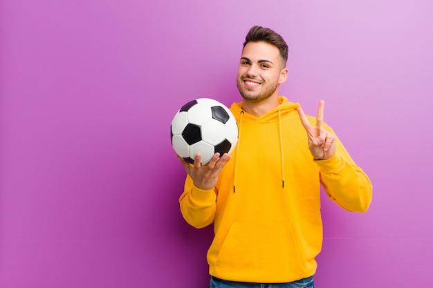 Junger hispanischer mann mit einem fußball gegen purpur