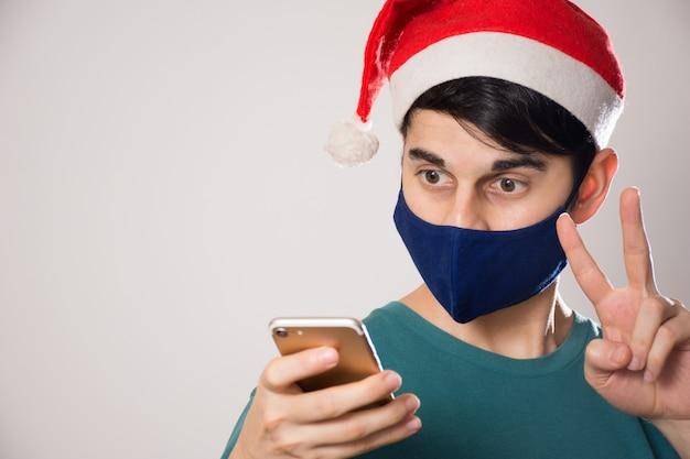 Junger hispanischer mann mit einer gesichtsmaske und einer weihnachtsmütze, die auf sein telefon schauen und eine friedensgeste tun