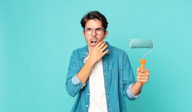 Junger hispanischer mann mit weit geöffnetem mund und augen und hand am kinn und hält eine farbrolle