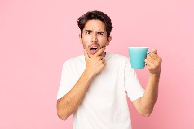 Junger hispanischer mann mit weit geöffnetem mund und augen und hand am kinn und hält eine kaffeetasse