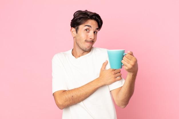 Junger hispanischer mann zuckt mit den schultern, fühlt sich verwirrt und unsicher und hält eine kaffeetasse