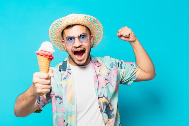 Junger hispanischer reisender mann, der erfolgreich einen sieg feiert und ein eis hält