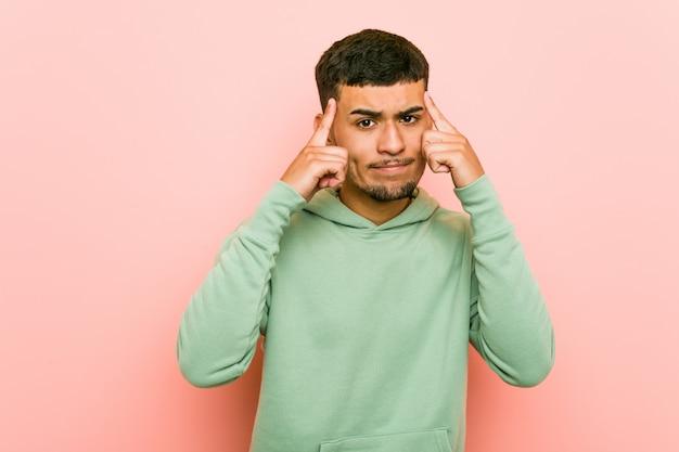 Junger hispanischer sportmann konzentrierte sich auf eine aufgabe und hielt die zeigefinger, die kopf zeigen.