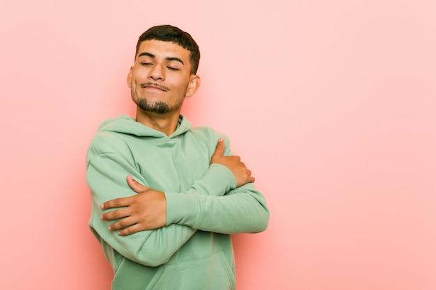Junger hispanischer sportmann umarmt, lächelt sorglos und glücklich.