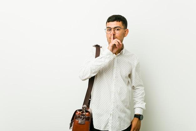 Junger hispanischer zufälliger geschäftsmann, der ein geheimnis hält oder um ruhe bittet.