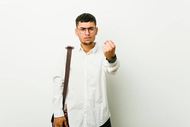 Junger hispanischer zufälliger geschäftsmann, der faust, aggressiven gesichtsausdruck zeigt.