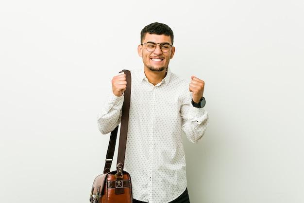 Junger hispanischer zufälliger geschäftsmann, der faust anhebt, glücklich und erfolgreich sich fühlt. sieg-konzept.