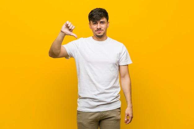 Junger hispanischer zufälliger mann, der eine abneigungsgeste, daumen unten zeigt. uneinigkeit konzept.