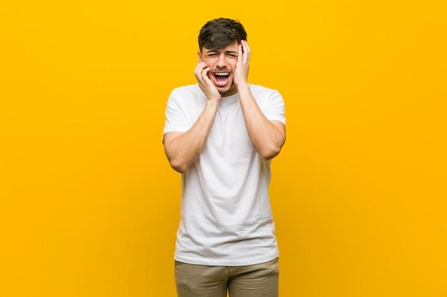 Junger hispanischer zufälliger mann, der trostlos jammert und schreit.