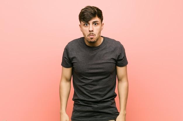 Junger hispanischer zufälliger mann zuckt mit den schultern und die offenen augen, die verwirrt werden.