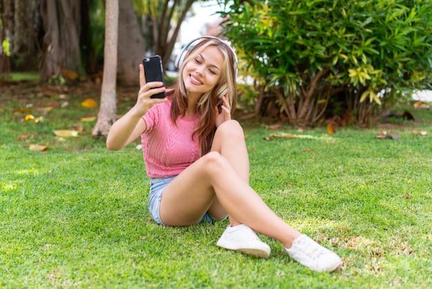 Junger hochschulabsolvent über isoliertem blauem hintergrund lachen