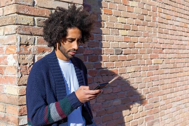 Junger hübscher afrikanischer mann, der seinen smartphone mit lächeln beim auf einer gemauerten wand am sonnigen tag draußen sich lehnen verwendet
