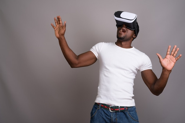 Junger hübscher afrikanischer mann, der virtual-reality-headset gegen verwendet