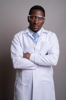 Junger hübscher afrikanischer mannarzt, der schutzbrille aga trägt