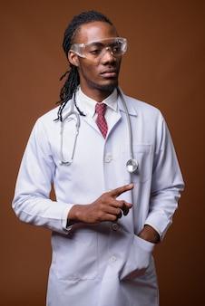 Junger hübscher afrikanischer mannarzt, der schutzbrille trägt