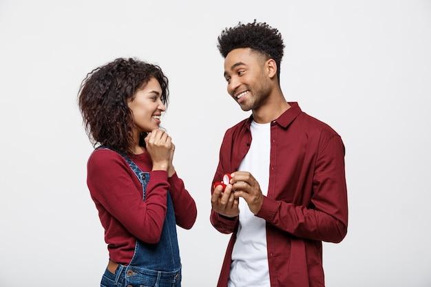 Junger hübscher afroamerikanermann bitten überraschend ihre freundin für antrag.