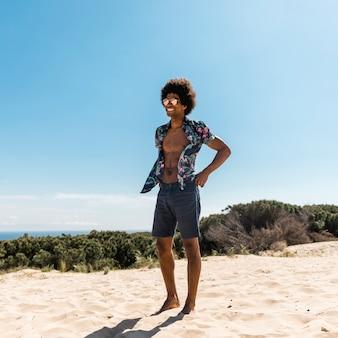 Junger hübscher afroamerikanermann, der auf strand aufwirft