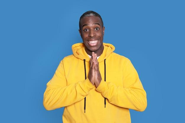 Junger hübscher afroamerikanermann, der lässigen pullover über blauem hintergrund trägt