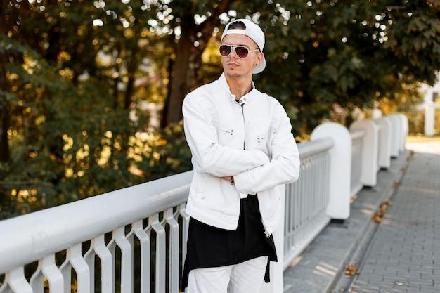 Junger hübscher amerikanischer hipster-mann in einer stilvollen weißen jacke mit sonnenbrille in einem modischen schwarzen t-shirt in den trendigen jeans wirft in einem park an einem sonnigen sommertag auf.
