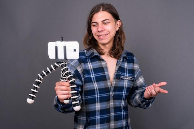 Junger hübscher androgyner hipster-mann mit langen haaren gegen graue wand