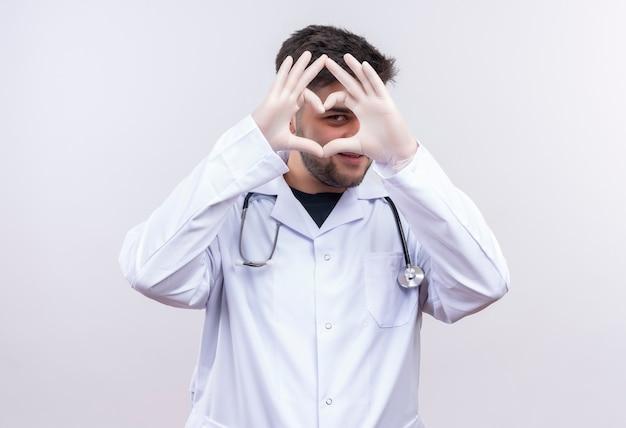 Junger hübscher arzt, der weiße medizinische handschuhe des weißen medizinischen kleides und das stethoskop trägt, das schüchtern das liebeszeichen mit den händen betrachtet, die über weißer wand stehen