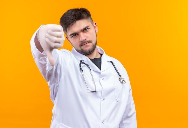Junger hübscher arzt, der weiße medizinische handschuhe des weißen medizinischen kleides und das stethoskop trägt, das unglückliche daumen unten tut, die über orange wand stehen