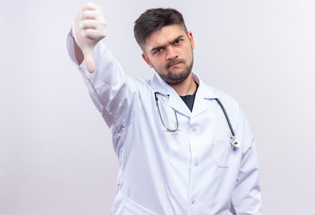 Junger hübscher arzt, der weiße medizinische handschuhe des weißen medizinischen kleides und das stethoskop trägt, das vorwurfsvoll schlechte daumen nach unten tut, die über weißer wand stehen