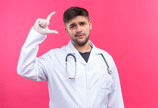 Junger hübscher arzt, der weiße medizinische handschuhe des weißen medizinischen kleides und des stethoskops trägt, verwirrte maßgröße mit den fingern, die über rosa wand stehen