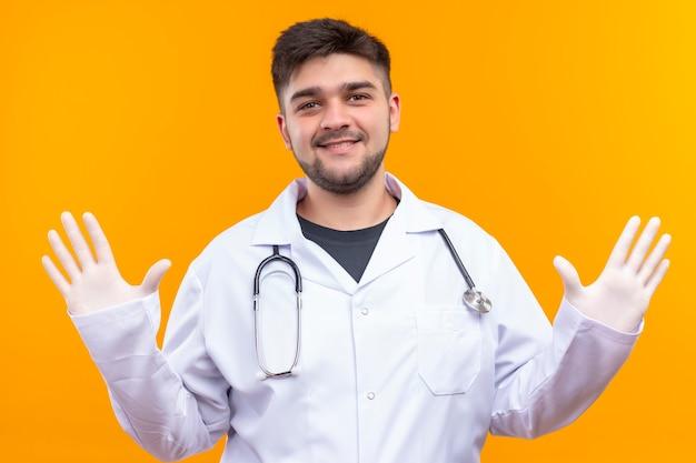 Junger hübscher arzt, der weiße medizinische handschuhe des weißen medizinischen kleides und lächelnde öffnende arme des stethoskops trägt und hallo sagt, das über orange wand steht