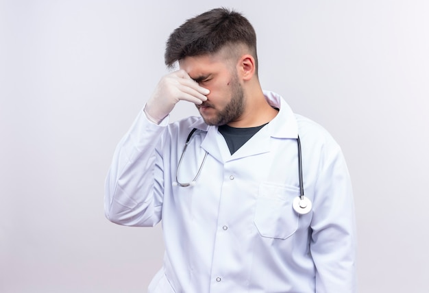 Junger hübscher arzt, der weiße medizinische handschuhe des weißen medizinischen kleides und stethoskop trägt, das seine laufende nase schließt, die über weißer wand steht