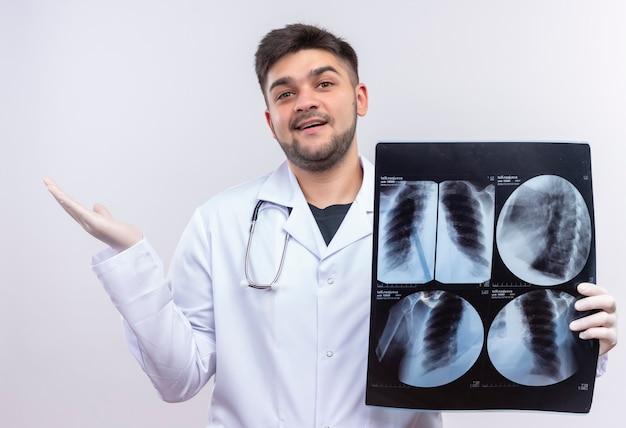Junger hübscher arzt, der weiße medizinische handschuhe des weißen medizinischen kleides und stethoskop trägt, froh mit ergebnissen der tomographie, die über weißer wand stehen