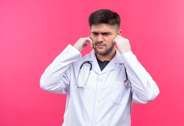 Junger hübscher arzt, der weiße medizinische handschuhe des weißen medizinischen kleides und stethoskop unzufrieden trägt, schloss seine ohren mit den händen, die über rosa wand stehen