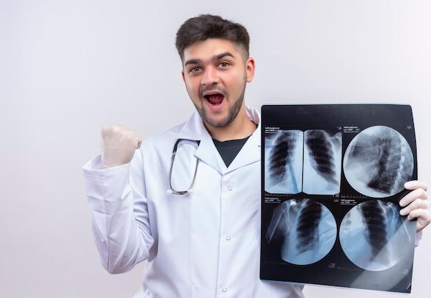 Junger hübscher arzt, der weiße medizinische handschuhe und stethoskop des weißen medizinischen kleides trägt, glücklich mit den tomographieergebnissen, die über weißer wand stehen