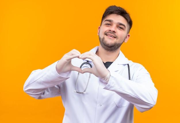 Junger hübscher arzt, der weiße medizinische handschuhe und stethoskop des weißen medizinischen kleides trägt und liebeszeichen mit den händen zeigt, die über orange wand stehen