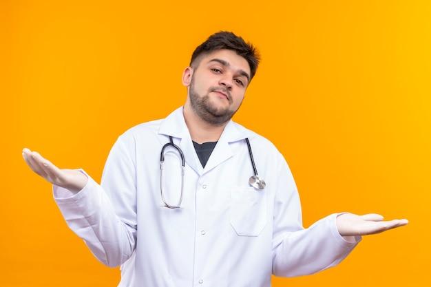 Junger hübscher arzt, der weißes medizinisches kleid weiße medizinische handschuhe und stethoskop trägt, kennt zeichen nicht