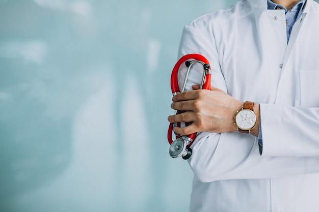 Junger hübscher arzt in einer medizinischen robe mit stethoskop
