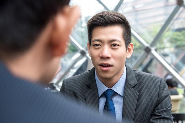 Junger hübscher asiatischer chinesischer geschäftsmann, der mit seinem partner spricht