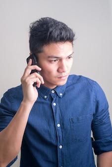 Junger hübscher asiatischer geschäftsmann, der am telefon spricht