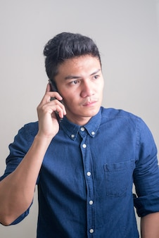 Junger hübscher asiatischer geschäftsmann, der beim telefonieren denkt