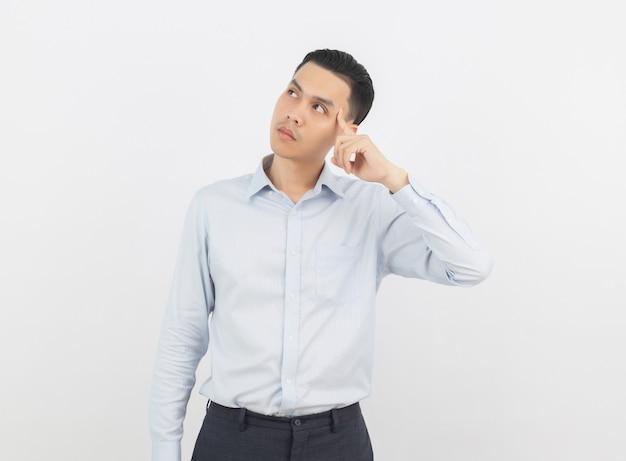 Junger hübscher asiatischer geschäftsmann, der eine idee beim oben schauen denkt