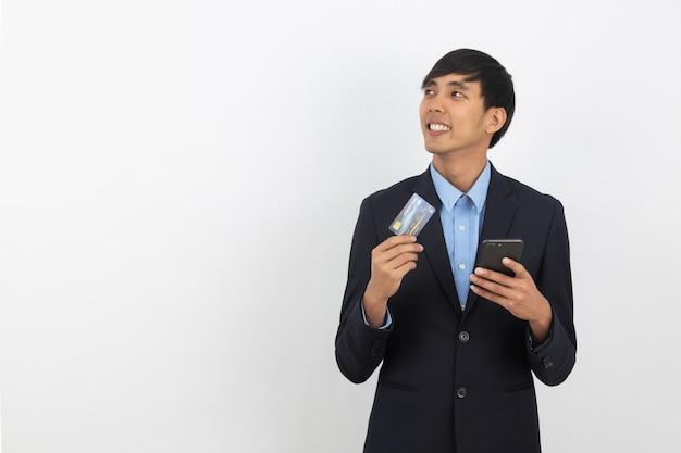 Junger hübscher asiatischer geschäftsmann, der einen schwarzen smartphone, eine kreditkarte hält und eine idee beim oben schauen denkt