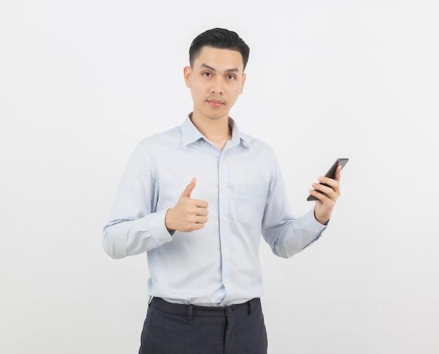 Junger hübscher asiatischer geschäftsmann, der einen schwarzen smartphone hält und sich daumen zeigt