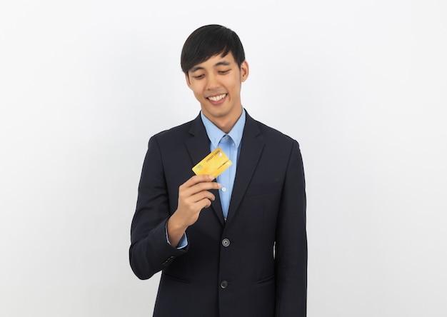 Junger hübscher asiatischer geschäftsmann, der kreditkarte hält und sucht