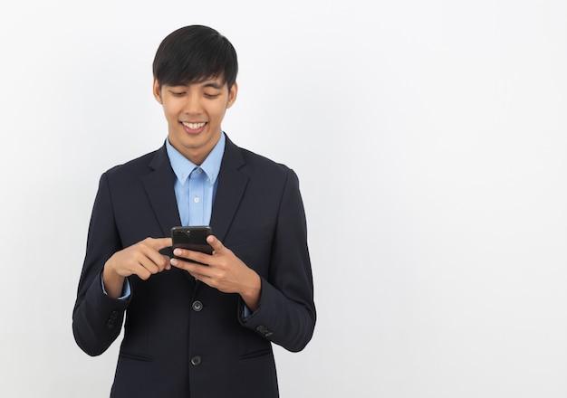Junger hübscher asiatischer geschäftsmann, der smartphone mit dem lächeln lokalisiert auf weiß spielt