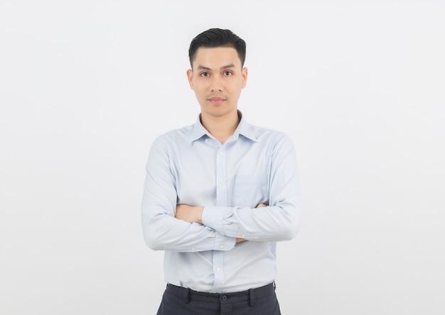 Junger hübscher asiatischer geschäftsmann, der zur kamera mit den armen gekreuzt schaut