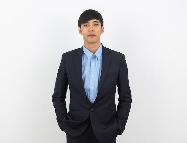 Junger hübscher asiatischer geschäftsmann, der zur kamera schaut