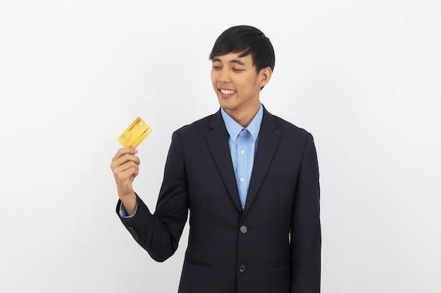 Junger hübscher asiatischer geschäftsmann, der zur kreditkarte hält und schaut