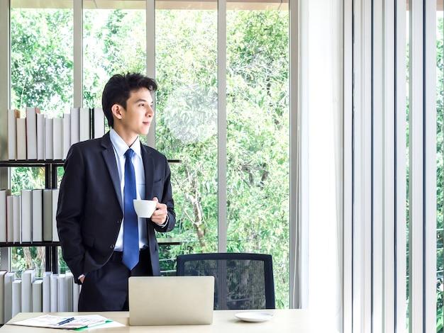 Junger hübscher asiatischer geschäftsmann im anzug, der kaffeetasse hält, die im büro steht und draußen schaut