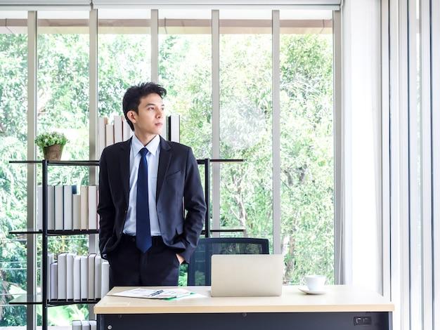 Junger hübscher asiatischer geschäftsmann im anzug steckte seine hände in taschen, die im büro stehen und nach draußen schauen